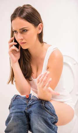 diarrea: Muchacha bonita en el inodoro con el teléfono celular y sonriente. Mujer sentada con el móvil en el baño en blanco