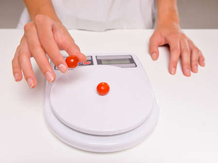 weighs: Close-up hands of young woman weighs a tomatoes. Concept of healthy food. Stock Photo