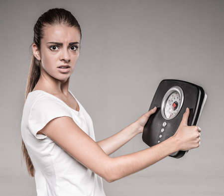 underweight: Frustrated woman with scale, on gray background. Stock Photo