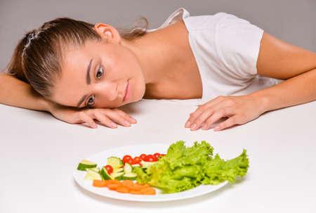 plato de ensalada: Joven mujer triste con un plato de ensalada. Foto de archivo