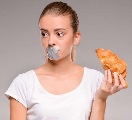 boca cerrada: Concepto de dieta: Mujer bastante joven con pastel de chocolate y la boca cerrada con cinta adhesiva.