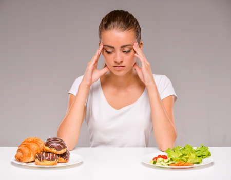 between: Difficult choice between junk and healthy food. Vegetables or sweets. Stock Photo
