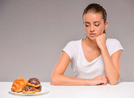 Young woman with plate of sweets. Concept of diet. Healthy food.