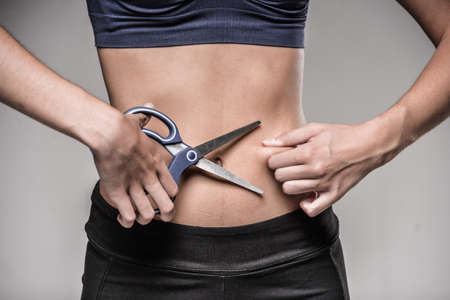 fat belly: Young skinny woman cuts her belly by scissors. Weight loss concept.