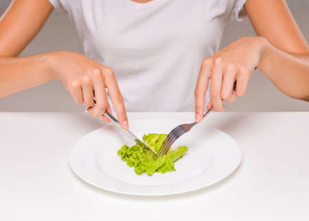 Healthy eating, vegetarian food, dieting. Young woman is eating a salad.