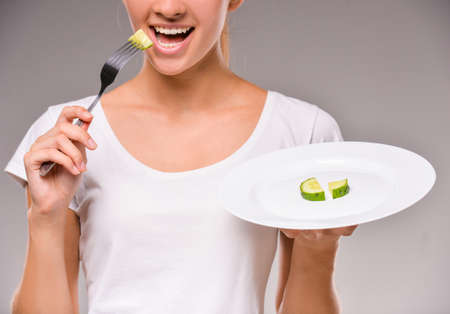 human hands: Healthy eating, vegetarian food, dieting. Young woman is eating a cucumber.