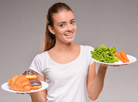 healthy food: Difficult choice between junk and healthy food. Vegetables or sweets. Stock Photo