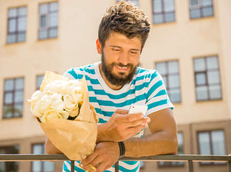 only man: Handsome young man with bouquet of flowers is waiting for his girlfriend. Stock Photo