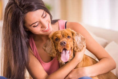 Happy young woman with dog are sitting on sofa. Stock Photo