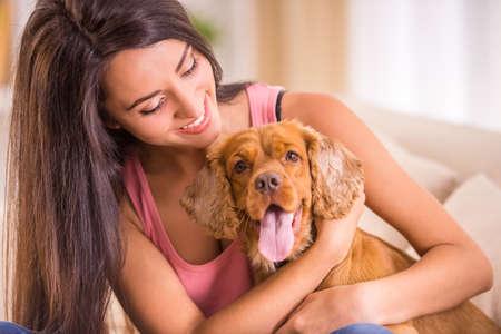 female dog: Mujer joven feliz con el perro est�n sentados en el sof�.