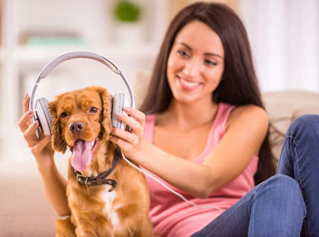 headphones: Young woman and her dog with headphone is listening a music. Stock Photo