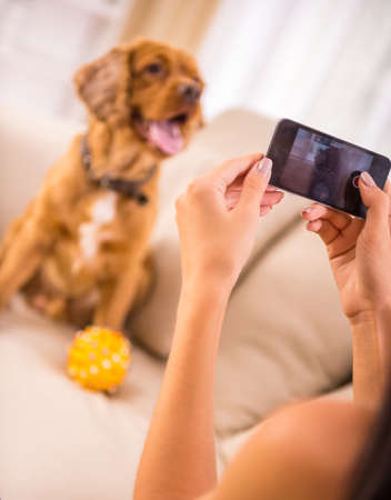 APARTMENT LIVING: Young woman is making a picture with her cute dog pet.