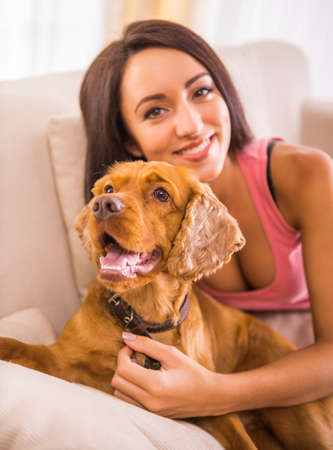 small dog: Young, attractive woman is playing with dog at home. Stock Photo