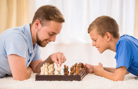 schooler: Father and son spend time together, are playing chess.