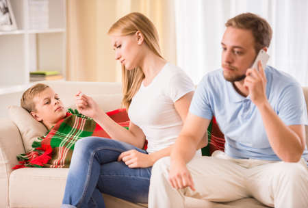 Loving parents take care of his son. Mother checking a temperature, father is calling to a doctor. Stock Photo