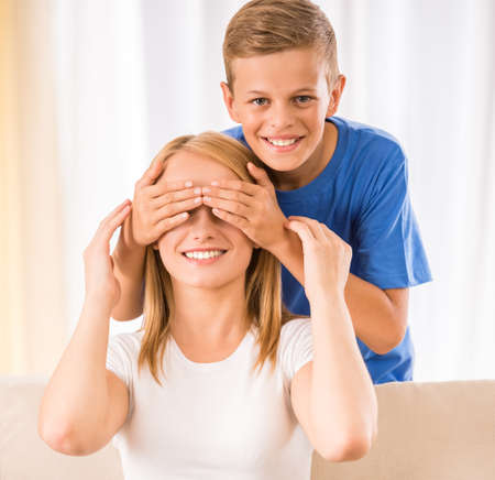 closes eyes: Smiling teen son closes eyes to his mom. Stock Photo