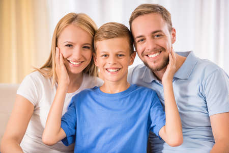 Young happy parent and their teenage son are posing at home, smiling. Banque d'images