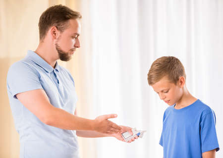 angry kid: Father is showing a cigarettes to his son. Stock Photo