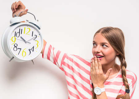 Young girl with a clock, standing on white background.