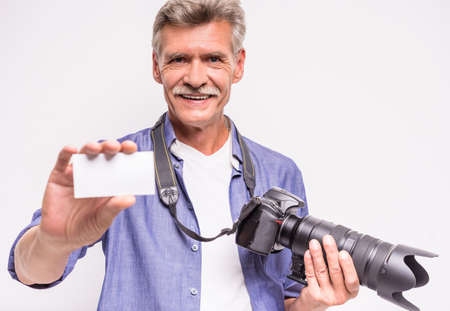 out of business: Portrait of senior man is holding camera and stretching out business card while standing against grey background. Stock Photo