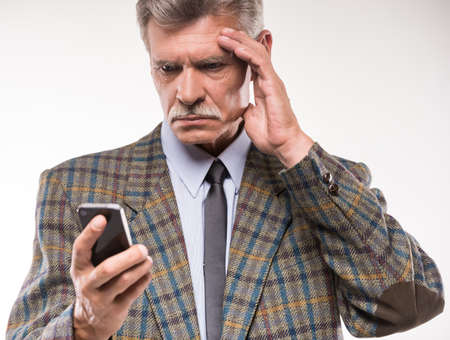 bad leadership: Portrait of senior man is suffering from headache, while looking at telephone.