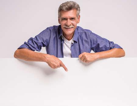 hombres maduros: Hombre mayor feliz que está sosteniendo el cartel en blanco sobre fondo blanco. Aquí puede ser su publicidad.