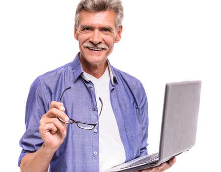 positivity: Senior man is using laptop, standing on white background.