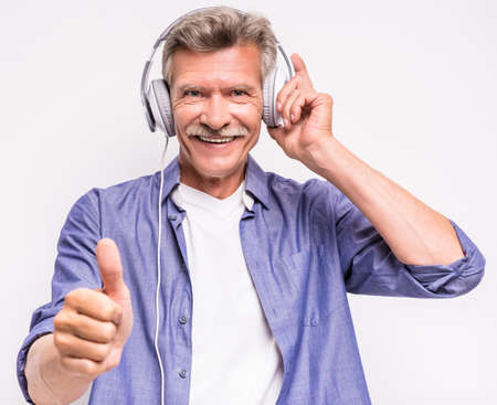 Portrait of smiling senior man in headphones listening to music and showing thumb up on grey background.