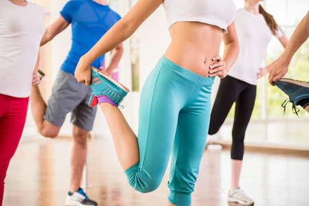 Fitness dance studio class. Group of people are exercising in dance studio.