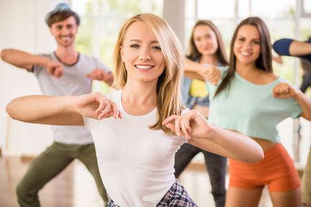 donna che balla: Giovani che ballano in palestra durante l'esercizio ballerino workout con nuova energia felice.