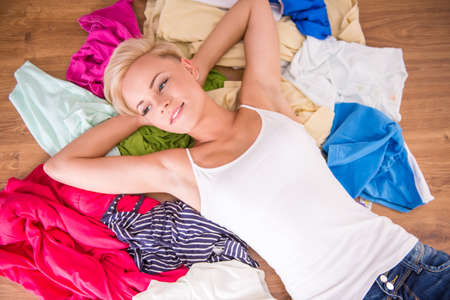 messy clothes: Top view of young woman is lying on the clothes.