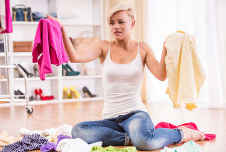 messy: Young woman is sitting on the floor with clothes lying near her. Stock Photo