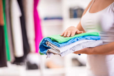 folding: Close-up hand of woman holding a pile of clothes. Stock Photo