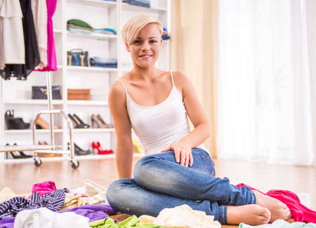 messy clothes: Young woman is sitting on the floor with clothes lying near her. Stock Photo