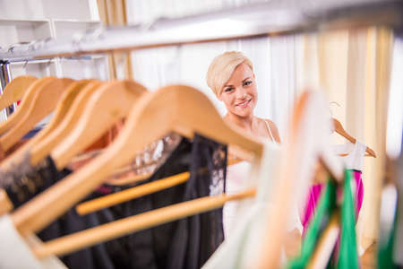 clothing store: Beautiful young woman in clothing store is smiling.