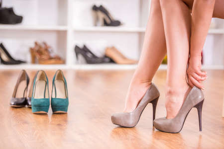 view an elegant wardrobe: Side view elegant lady is trying on shoes in wardrobe room. Stock Photo