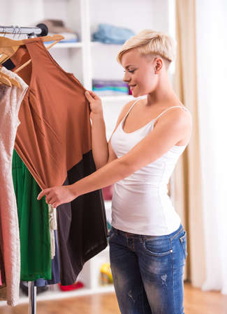 clothing store: Beautiful young woman is looking at a dress in clothing store. Stock Photo