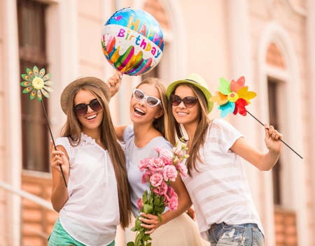Three beautiful young women celebrating a birthday, outdoors