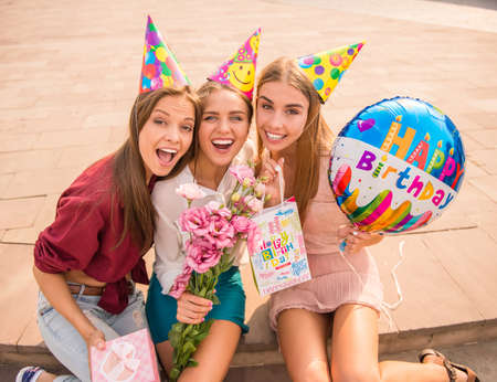 hen party: Three beautiful young women celebrating a birthday, outdoors