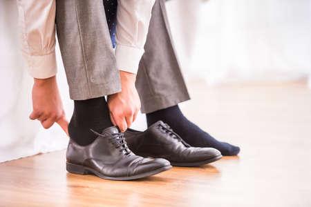 Jonge zakenman kleding schoenen in de slaapkamer thuis