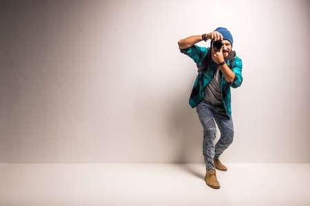 수염을 가진 젊은 쾌활한 사진 작가는 스튜디오에서 일하고있다.