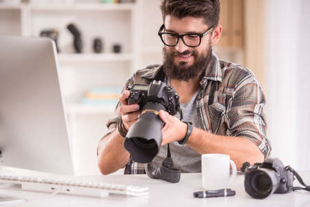 busy beard: Young cheerful photographer with beard, while working in his office