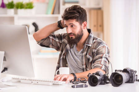 businessman working at his computer: Young cheerful photographer with beard, while working in his office