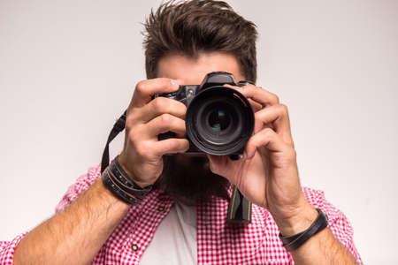 Junge fröhliche Fotografen mit Bart, während der Arbeit im Studio