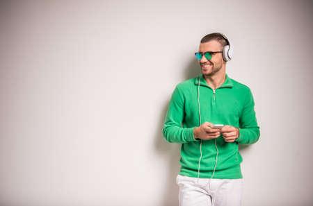 personas escuchando: Retrato de un hombre joven escuchando música en los auriculares en fondo gris Foto de archivo