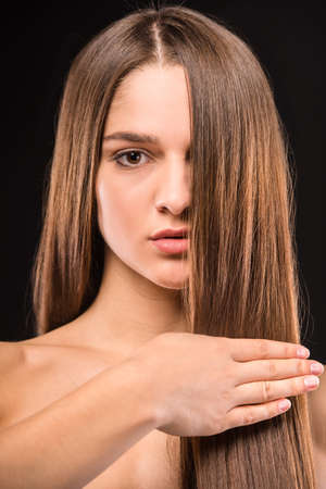 coloring lips: Portrait of a young beautiful woman with long hair, isolated on black background