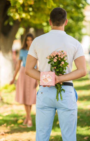 girl holding flower: Loving young couple on a date with flowers and with a gift in the park Stock Photo