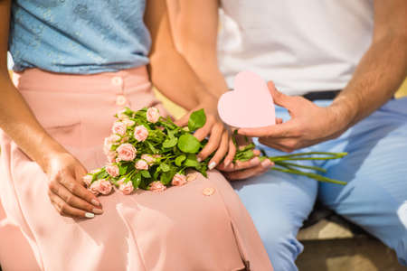 love couple: Loving young couple on a date with flowers and with a gift in the park Stock Photo