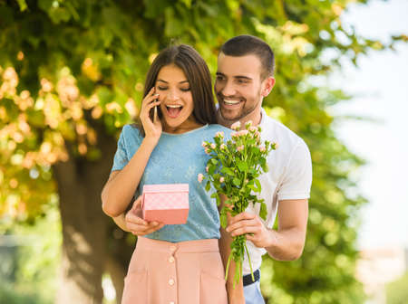 lovers park: Loving young couple on a date with flowers and with a gift in the park Stock Photo