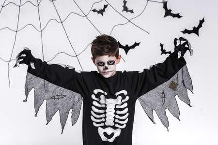 skeleton costume: Boy in a skeleton costume, Halloween celebration, on the background of bats and cobwebs